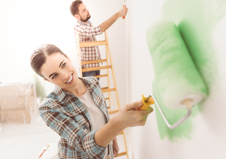 Happy couple painting walls in their new house: the man is standing on a ladder and the woman is using a paint roller and applying bright green paint