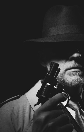 1950 년대 스타일 형사 어둠 속에서 포즈, 그는 무기를 들고 하 고 페도라 모자를 착용, 느와르 영화 캐릭터 스톡 콘텐츠