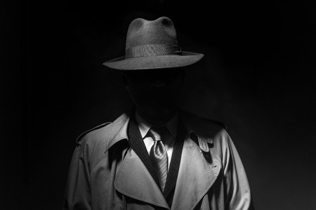 Mężczyzna pozujący w ciemności w kapeluszu fedora i trenczu, postać filmowa noir z lat 50