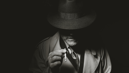 Noir film character standing in the dark and smoking a cigarette, he is wearing a fedora hat and a trench coat Foto de archivo