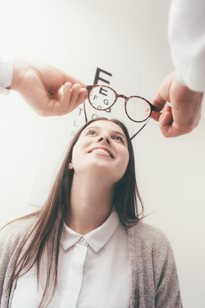 oculista: Young happy woman trying her new pair of glasses after the eye exam Foto de archivo