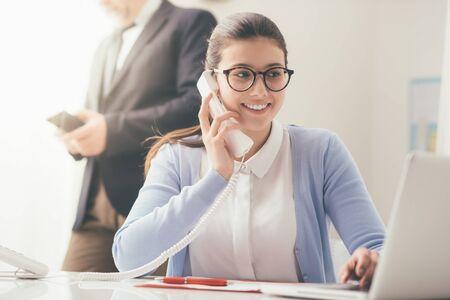 Efficiënte glimlachende secretaresse die telefoongesprekken beantwoordt en met klanten spreekt, zit zij bij bureau en werkt met laptop Stockfoto - 84116153