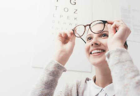 Gelukkige jonge vrouw die haar nieuwe glazen, oogzorgconcept proberen