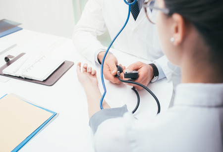 Doctor checking blood pressure of a patient, he is measuring heart pulses with a sphygmomanometer, healthcare and diagnostics concept Stock Photo