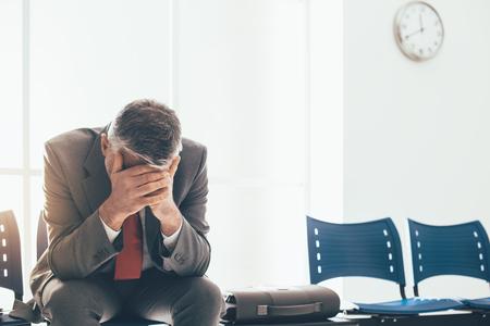 Verzweifelter Geschäftsmann im Warteraum mit Kopf in den Händen, wartet er auf ein Vorstellungsgespräch; Konzept der Arbeitslosigkeit und des Geschäftsausfalls