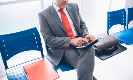 mobile app: Corporate businessman sitting in the waiting room and connecting with a digital touch screen tablet, he is waiting for a meeting