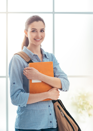 Young female college student portrait, she is smiling at camera and holding books, school and education concept
