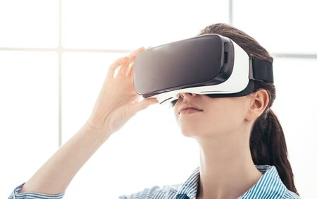Young woman experiencing virtual reality, she is wearing a VR headset, innovative technology concept