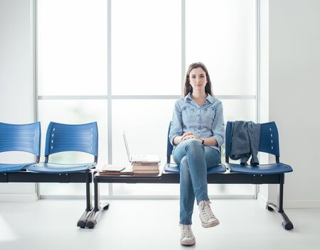 Young female student in the waiting room, she is pensive and waiting for an interview Stock Photo