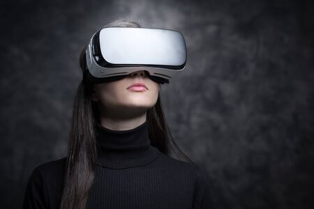 Girl wearing a VR headset and experiencing virtual reality, technology and innovation concept Stock Photo