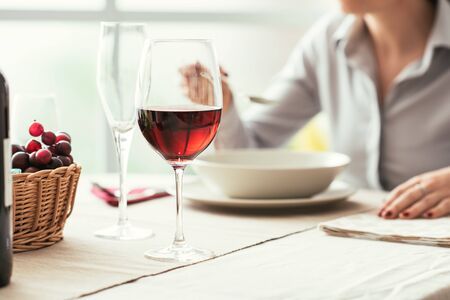 expensive: Woman having lunch at the restaurant and drinking a glass of red wine, fine dining and wine tasting concept