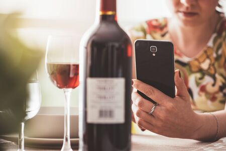 mobile app: Woman having lunch at the restaurant and using a wine app with his smartphone, she is scanning the wine bottle label Stock Photo