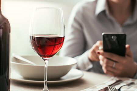 Woman using a smartphone at the restaurant and drinking red wine, fine dining and wine tasting concept
