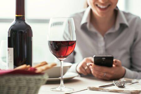 Vrouw die een smartphone gebruiken bij het restaurant en rode wijn, het fijne dineren en wijn proevende concept drinken