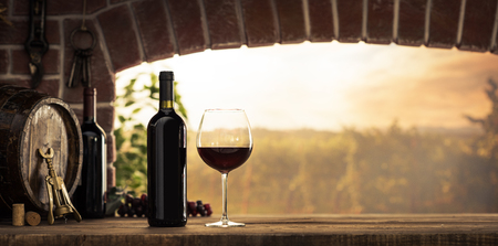 Red wine tasting in the wine cellar: wineglass and bottles next to the window and panoramic view of vineyards at sunset