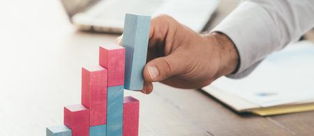 Geschäftsmann arbeitet am Schreibtisch, er baut eine wachsende finanzielle Grafik mit Holzspielzeug Blöcke: erfolgreiche Business-Konzept Standard-Bild