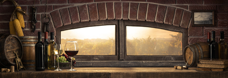 Wine glasses, bottles and barrels in a rustic countryside wine cellar; panoramic window view of lush vineyards at sunset: traditional winemaking concept