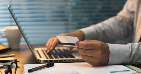Businessman doing online banking, he is making e-payments with a credit card and his laptop, online business and finance concept Stock Photo
