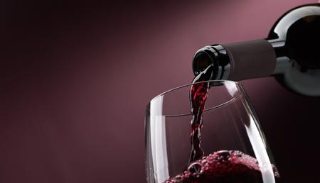 Giet rode wijn van een fles in een wijnglas: wijnproeverij en viering Stockfoto