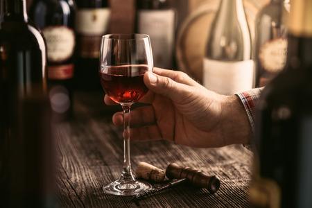 Wijnproeverij in de rustieke kelder en wijnbar: sommelier met een glas heerlijke rode wijn en uitstekende wijnflessencollectie op de achtergrond
