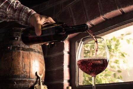Sommelier pouring wine into a balloon glass in the cellar: wine tasting and traditional winemaking concept 版權商用圖片 - 84267331