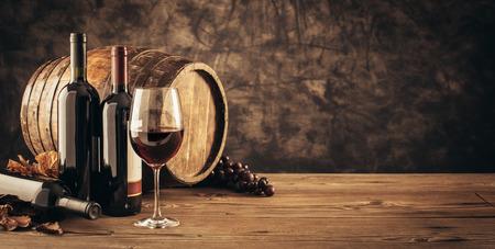 Wijnglas, houten vat en verzameling uitstekende rode wijnflessen in de kelder: traditioneel wijnmaken en wijnproeverij