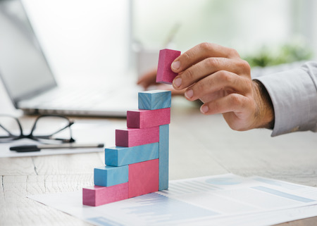 Homme d'affaires travaillant au bureau, il construit un graphique financier croissant utilisant des blocs de jouets en bois: concept d'entreprise prospère Banque d'images - 84267384