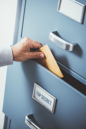 Businessman putting an envelope into a top secret classified drawer, data protection and storage concept Banco de Imagens