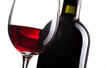 Excellent red wine tasting: wine bottle and wineglass on white background, close up