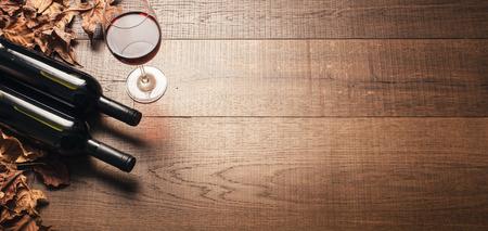 레드 와인 병, 와인 글라스와 마른 포도 나무 소박한 나무 테이블에 나뭇잎 : 와인 시음 및가 개념