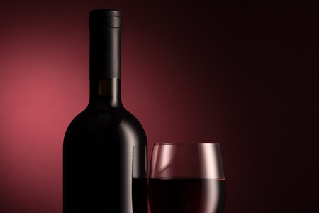 Luxury red wine tasting and celebration: wine bottle and full glass on red background