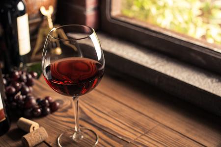 おいしい赤ワインのセラー、ワインのガラス ウィンドウと、背景に緑豊かなブドウの木の横にあるボトルで試飲