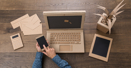 Businessman working in a creative eco-friendly office made from cardboard, he is using a laptop and a smartphone, top view