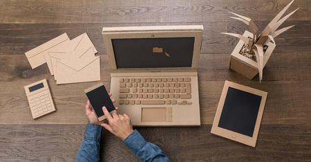 Zakenman die in een creatief milieuvriendelijk die bureau werken van karton wordt gemaakt, gebruikt hij laptop en een smartphone, hoogste mening