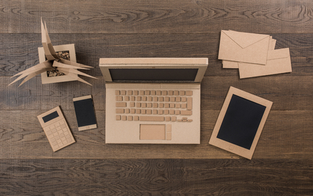 Creative eco-friendly office items, laptop, tablet and smartphone handmade using recycled cardboard, top view