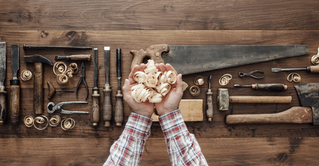 Professional carpenter holding wood shavings and vintage woodworking tools on a workbench, top view Banque d'images