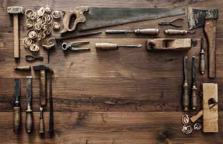 Frame composed of a collection of vintage woodworking tools on a workbench: carpentry, craftsmanship and handwork concept, flat lay