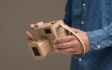 Photographer holding an handmade eco-friendly cardboard camera, crafts and creativity concept