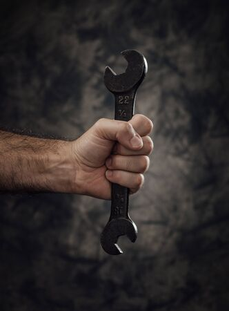 Manual worker holding a spanner on dark background, empowerment and workers rights concept