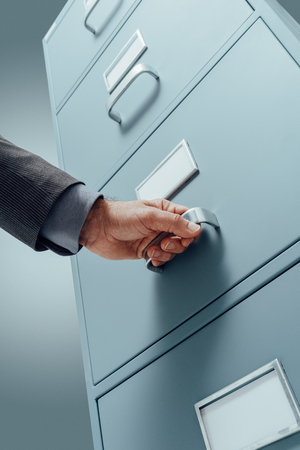 Office clerk searching files in a filing cabinet drawer, business administration and data storage concept