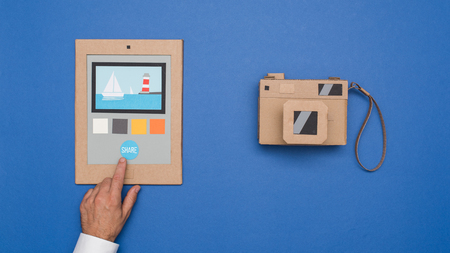 User editing photos on a cardboard tablet and handmade carton camera, crafts and creativity concept
