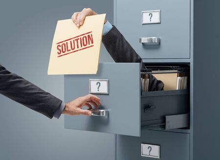 Businessman inside a filing cabinet giving a file with business solutions to an office clerk: strategy, problem solving and planning concept
