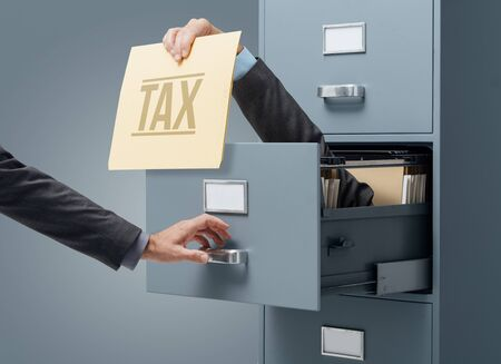 Businessman inside a filing cabinet giving a tax file to an office clerk: tax refunds, payments and deadlines concept