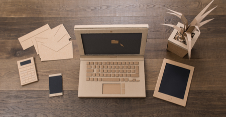Creative eco-friendly office desk items, laptop, tablet and smartphone handmade using recycled cardboard, top view Stock Photo