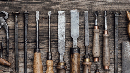 Collection of old woodworking and carving tools on a rough vintage table: carpentry, craftsmanship and handwork concept, flat lay