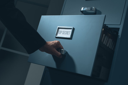 Office worker searching top secret confidential information in the office late at night, data theft and security concept