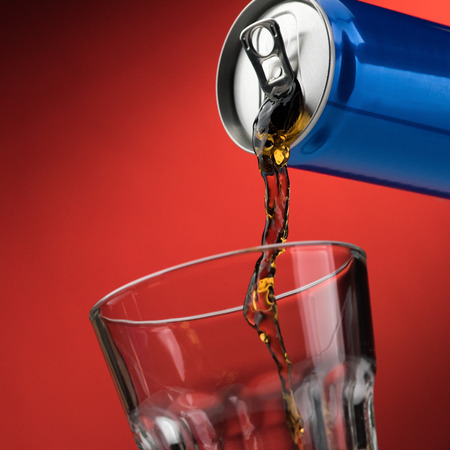 Pouring a refreshing sugary soft drink from a can into a glass Stock Photo