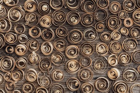 Wood spiral shavings on a vintage workbench background: carpentry, woodworking and craftsmanship concept