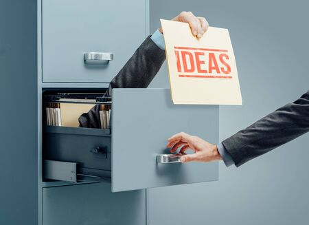Businessman inside a filing cabinet giving a file with innovative ideas to an office worker: business development and solutions concept