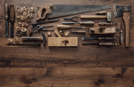 Collection of vintage woodworking tools on a rough workbench and blank copy space: carpentry, craftsmanship and handwork concept, flat lay Stock Photo